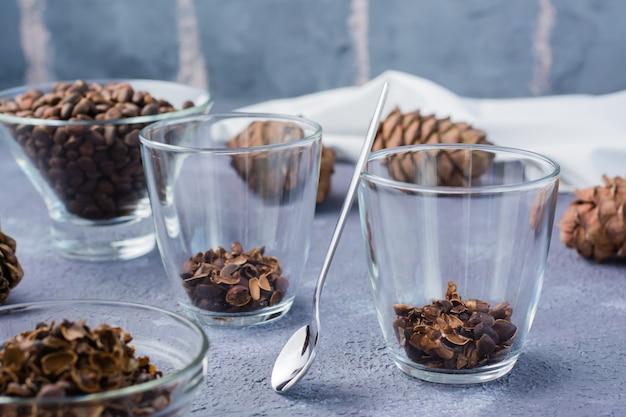 Łupiny orzeszków piniowych w szklankach gotowe do wywaru na stole. medycyna alternatywna