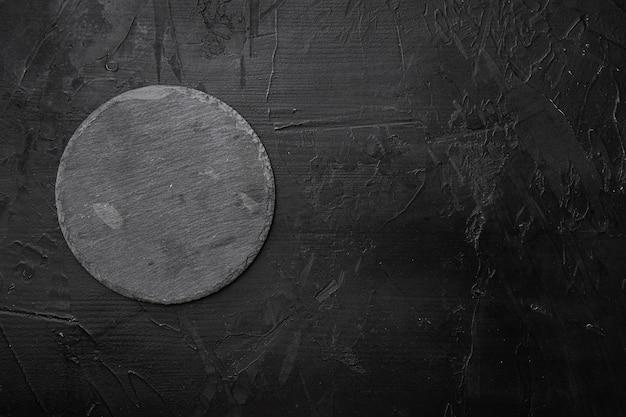 Łupkowa deska do krojenia z kopią miejsca na tekst lub jedzenie z kopią miejsca na tekst lub jedzenie, widok z góry płasko leżący, na czarnym tle ciemnego kamiennego stołu