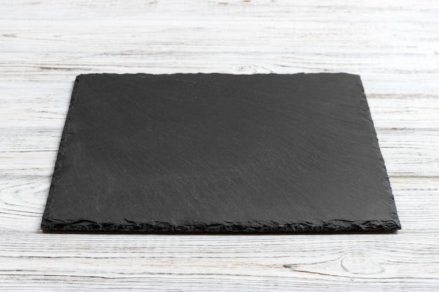 Łupkowa deska nad starym drewnianym tłem z kopii przestrzenią