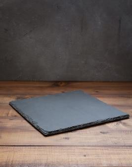 Łupkowa kamienna taca przy drewnianym stole, z teksturą tła ściany