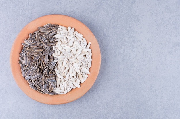 Łuskane nasiona słonecznika na talerzu na marmurze.