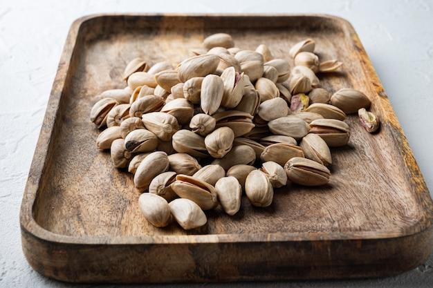 Łuskane, niesolone pistacje, na białym tle z teksturą