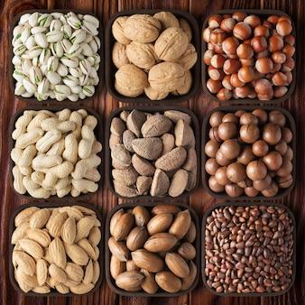 Łuskane orzechy na tle drewnianym stole. skład zdrowej żywności: orzechy pekan, orzechy laskowe, orzechy włoskie, pistacje, migdały, makadamia, orzeszki ziemne, sosna, brazylijskie.