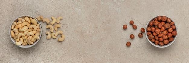 Łuskane orzechy nerkowca i laskowe. baner z orzechami. orzechy w spodku na kamiennym blacie, widok z góry. miejsce na wstawienie tekstu lub projektu.