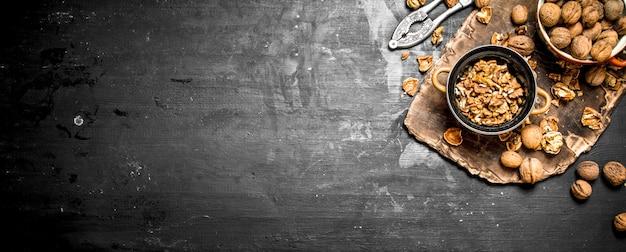 Łuskane orzechy włoskie w misce z dziadkiem do orzechów.