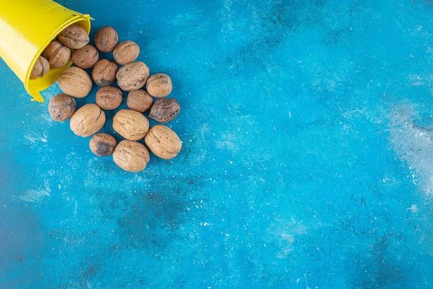 Łuskane orzechy włoskie w wiadrze, na niebieskim stole.