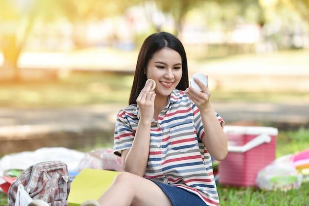 Lustro kobieta makijaż kosmetyki uśmiechnięta młoda dziewczyna makijaż twarz na zewnątrz w proszku make-up kobieta patrzeć w lustro osobiście