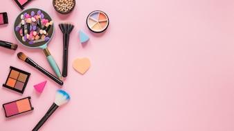 Lustro z cieniami do powiek i szczotkami na różowym stole