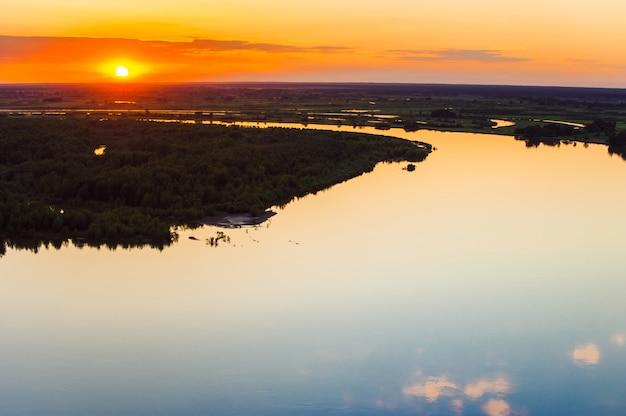 Lustrzana powierzchnia wody o zachodzie słońca. region ałtaj. wyspy na rzece.