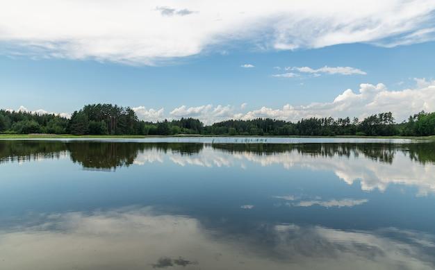 Lustrzane błękitne niebo z białymi chmurami i lasem na powierzchni jeziora