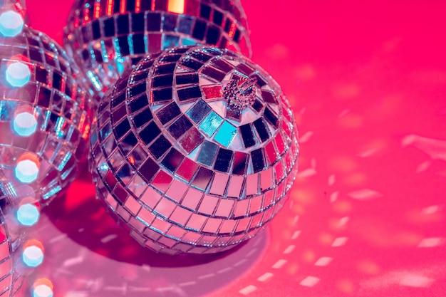 Lustrzane dyskotekowe piłki nad różowym tłem. impreza, koncepcja życia nocnego