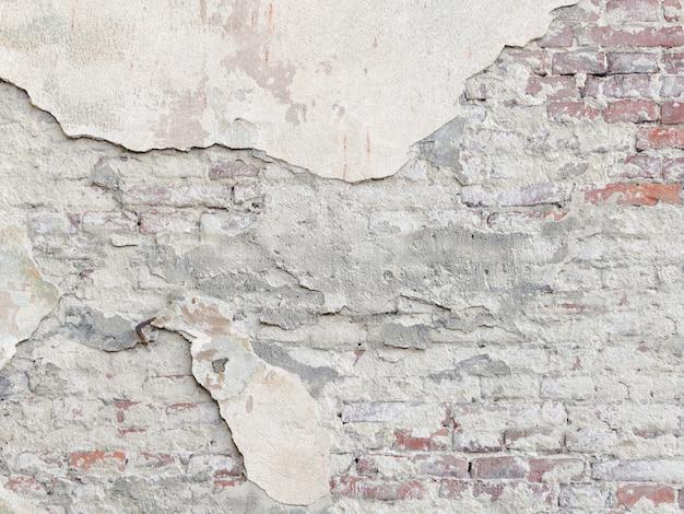 Łuszcząca się ściana z czerwonej cegły pod tynkiem. tło