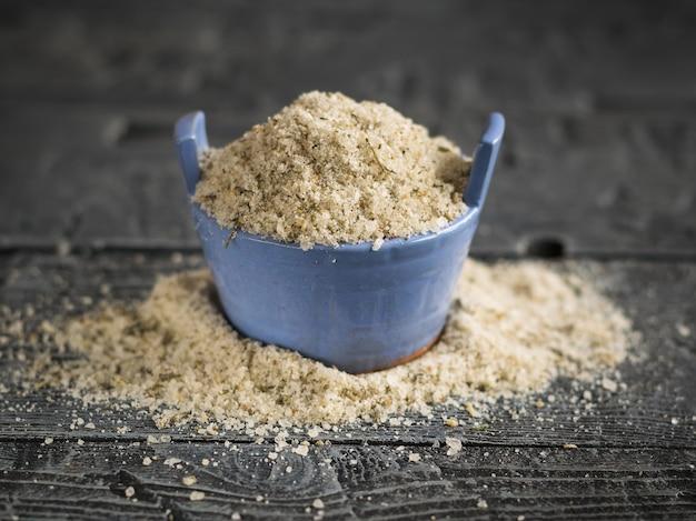 Łuszcząca się sól morska z ziołami w niebieskim pucharze na drewnianym stole.