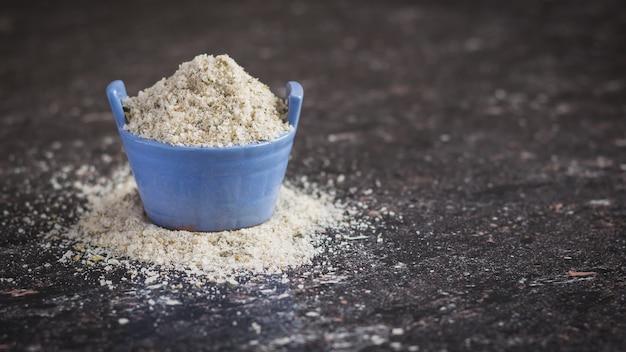 Łuszcząca się sól morska z ziołami w niebieskim pucharze na kamiennym stole.