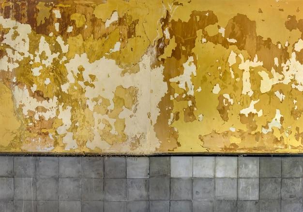 Łuszcząca się tekstura farby. powierzchnia ściany grunge z pękniętą i obraną żółtą farbą i szarymi płytkami