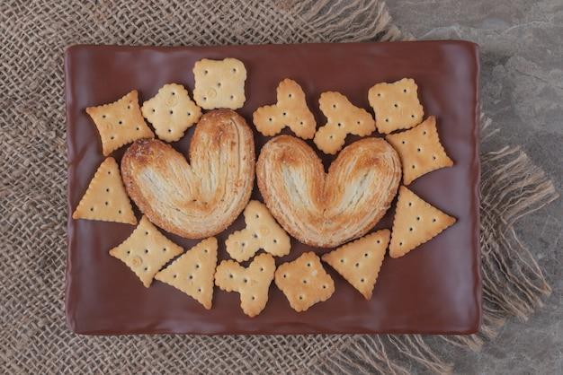 Łuszczące się ciasteczka i krakersy leżą na marmurowym talerzu
