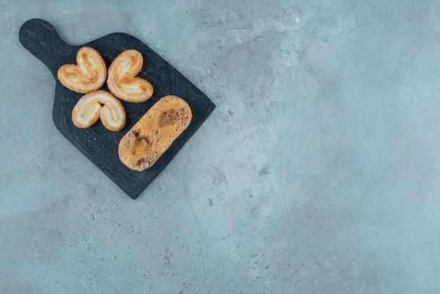 Łuszczące się ciasteczka i mały tort na desce na marmurowym tle. wysokiej jakości zdjęcie