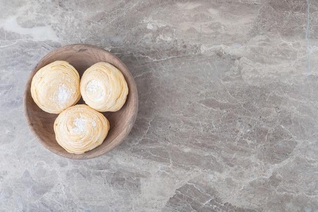 Łuszczące się ciasteczka w małej misce na marmurowej powierzchni