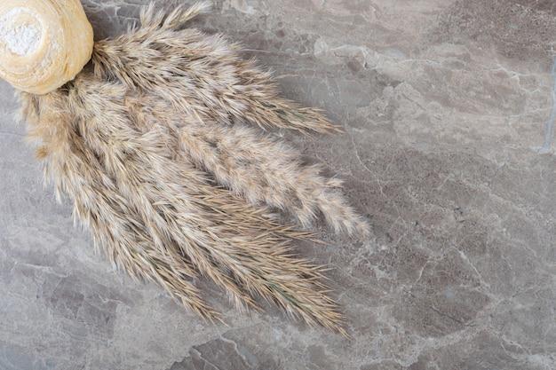 Łuszczące się ciasteczko i wiązka łodyg trawy iglastej na marmurowej powierzchni
