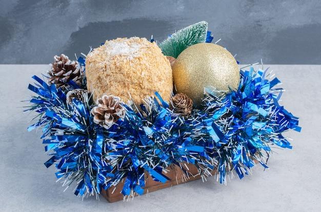 Łuszczące się ciasto umieszczone na wiązce świątecznych dekoracji na marmurowej powierzchni