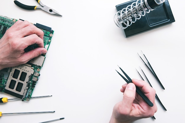 Lutowanie elementów komputera na płasko. widok z góry na ręce mechanika mocowania uszkodzonej części w płycie głównej laptopa. naprawa elektroniki, budowa, koncepcja biznesowa