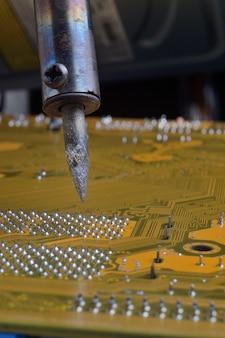 Lutowanie płytek elektronicznych z elementami elektronicznymi. inżynierowie naprawiają płytkę drukowaną za pomocą lutownicy.