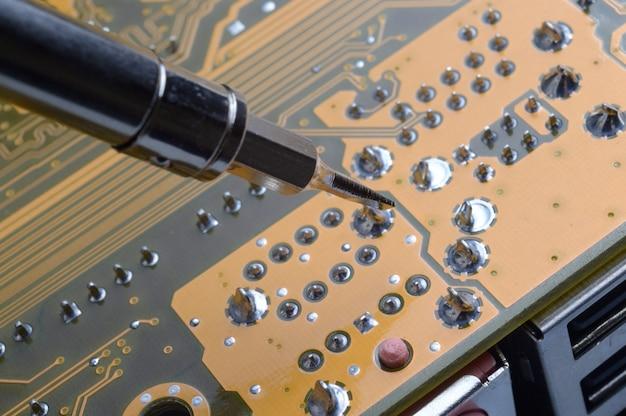 Lutowanie Płytek Elektronicznych Z Elementami Elektronicznymi. Inżynierowie Naprawiają Płytkę Drukowaną Za Pomocą Lutownicy. Premium Zdjęcia