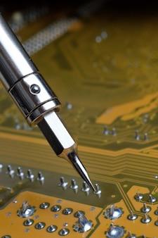 Lutowanie płytki drukowanej z elementami elektronicznymi. inżynierowie naprawiają płytkę drukowaną za pomocą lutownicy.