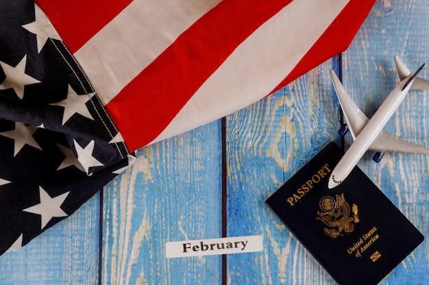 Luty, miesiąc kalendarzowy, turystyka, emigracja, amerykańska flaga usa z paszportem amerykańskim i model samolotu pasażerskiego