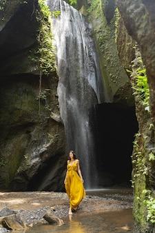 Luźna atmosfera. miła brunetka pokazuje swoją żółtą sukienkę podczas wizyty