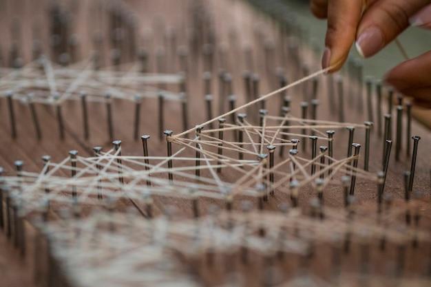 Luźny koniec przywiązany do drewnianej deski z gwoździami, koncepcja tekstylna rzemieślnicza.
