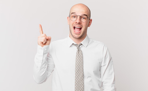 Łysy biznesmen czując się jak szczęśliwy i podekscytowany geniusz po zrealizowaniu pomysłu, radośnie podnosząc palec, eureka!