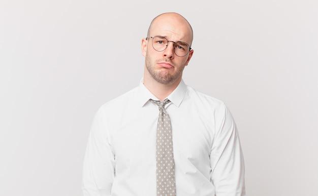 Łysy biznesmen czuje się smutny i marudny z nieszczęśliwym spojrzeniem, płacze z negatywnym i sfrustrowanym nastawieniem