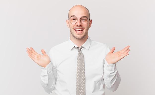 Łysy biznesmen czuje się szczęśliwy, podekscytowany, zaskoczony lub zszokowany, uśmiechnięty i zdumiony czymś niewiarygodnym