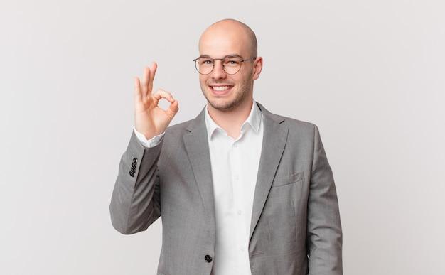 Łysy biznesmen czuje się szczęśliwy, zrelaksowany i zadowolony, okazując aprobatę dobrym gestem, uśmiechnięty