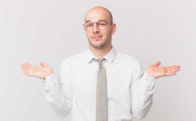 Łysy biznesmen czuje się zakłopotany i zdezorientowany, wątpi, waży lub wybiera różne opcje ze śmiesznym wyrazem twarzy