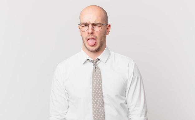 Łysy biznesmen czuje się zdegustowany i zirytowany, wystawia język, nie lubi czegoś paskudnego i obrzydliwego