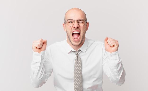 Łysy biznesmen krzyczy agresywnie z gniewnym wyrazem twarzy lub z zaciśniętymi pięściami świętuje sukces