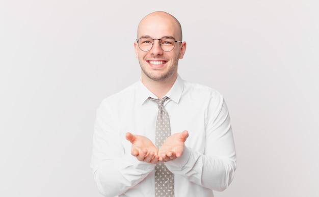 Łysy biznesmen uśmiechający się radośnie z przyjaznym, pewnym siebie, pozytywnym spojrzeniem, oferujący i pokazujący przedmiot lub koncepcję