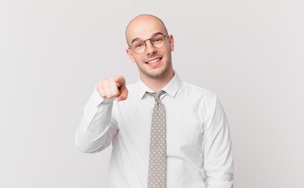 Łysy biznesmen wskazujący na przód z zadowolonym, pewnym siebie, przyjaznym uśmiechem, wybierający ciebie