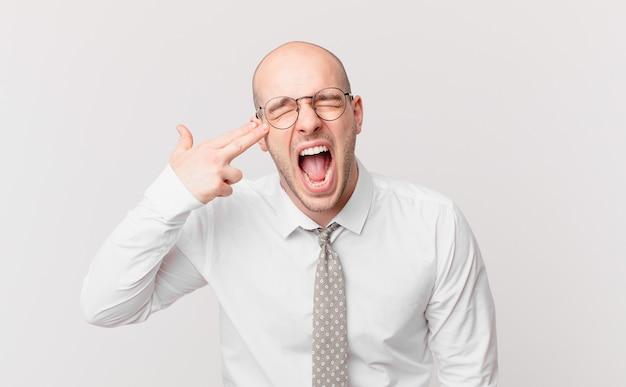 Łysy biznesmen wyglądający na niezadowolonego i zestresowanego, samobójczy gest wykonujący znak pistoletu ręką, wskazujący na głowę