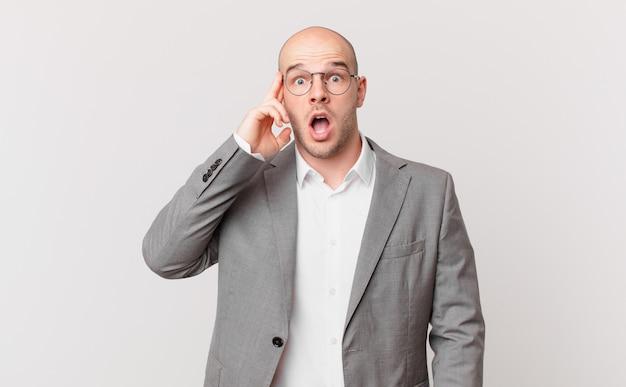 Łysy biznesmen wyglądający na zaskoczonego, z otwartymi ustami, zszokowany, realizujący nową myśl, pomysł lub koncepcję