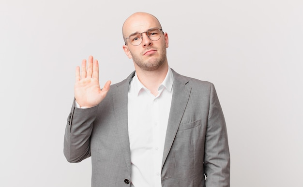 Łysy biznesmen wyglądający poważnie, surowo, niezadowolony i zły, pokazując otwartą dłoń, wykonując gest zatrzymania