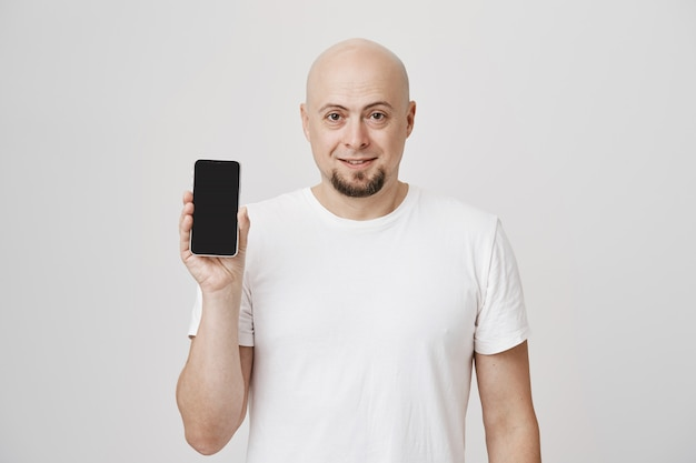 Łysy brodaty facet w średnim wieku w białej koszulce przedstawiającej aplikację na smartfona