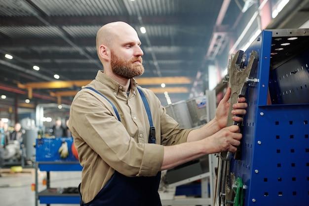 Łysy, brodaty inżynier w odzieży roboczej wybiera ogromny klucz przemysłowy do wykonywania prac technicznych w fabryce