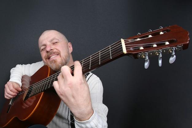 Łysy brodaty mężczyzna gra na gitarze klasycznej