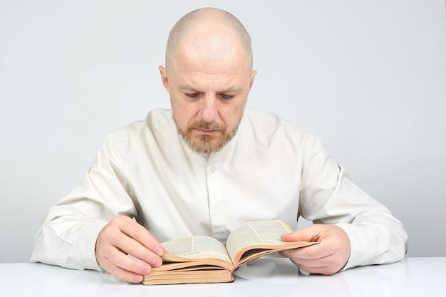 Łysy, brodaty mężczyzna w jasnych ubraniach, czytający biblię