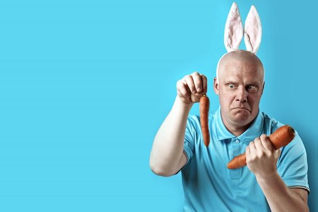 Łysy, brutalny mężczyzna w lekkich t-shirtach i uszach królika. w rękach trzyma marchewkę o innym rozmiarze.