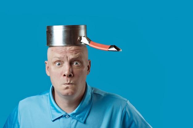 Łysy, brutalny mężczyzna w niebieskiej koszulce postawił na głowie garnek