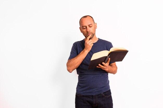 Łysy dorosły mężczyzna recenzuje obszerną książkę do nauki